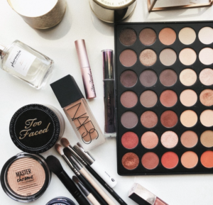 A collection of makeup products including a makeup palette