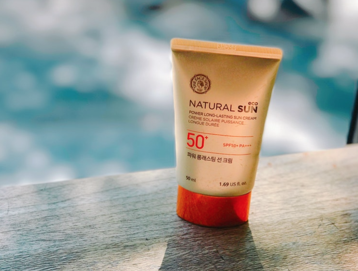 A tube of sunscreen by a swimming pool