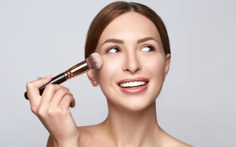 a woman applying makeup with a powder brush to her cheek.