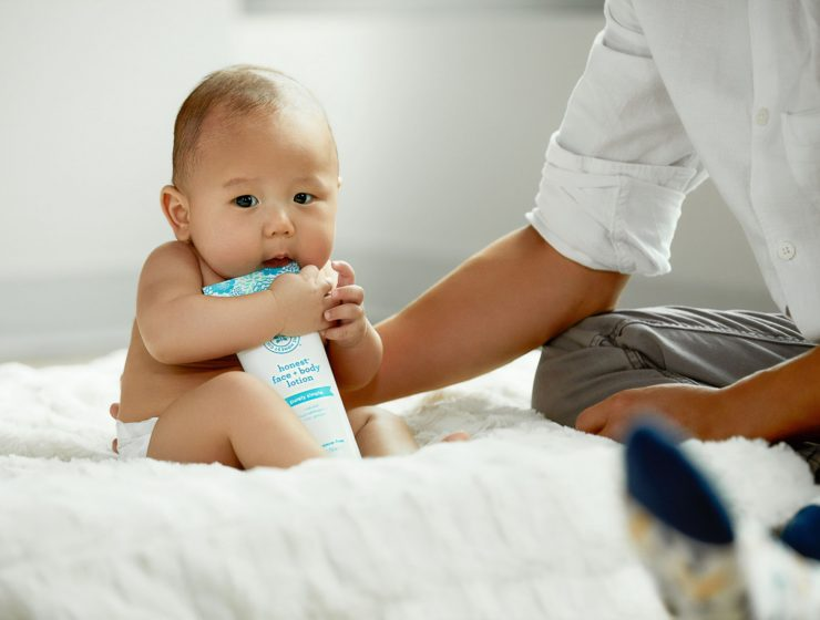 baby sat next to parent whilst holding-on-tight to a bottle of body lotion.