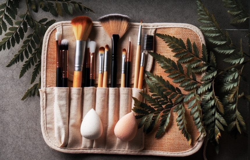 choosing Eco-friendly: bamboo makeup brushes within a brush roll pack, leaves to the side on a black background