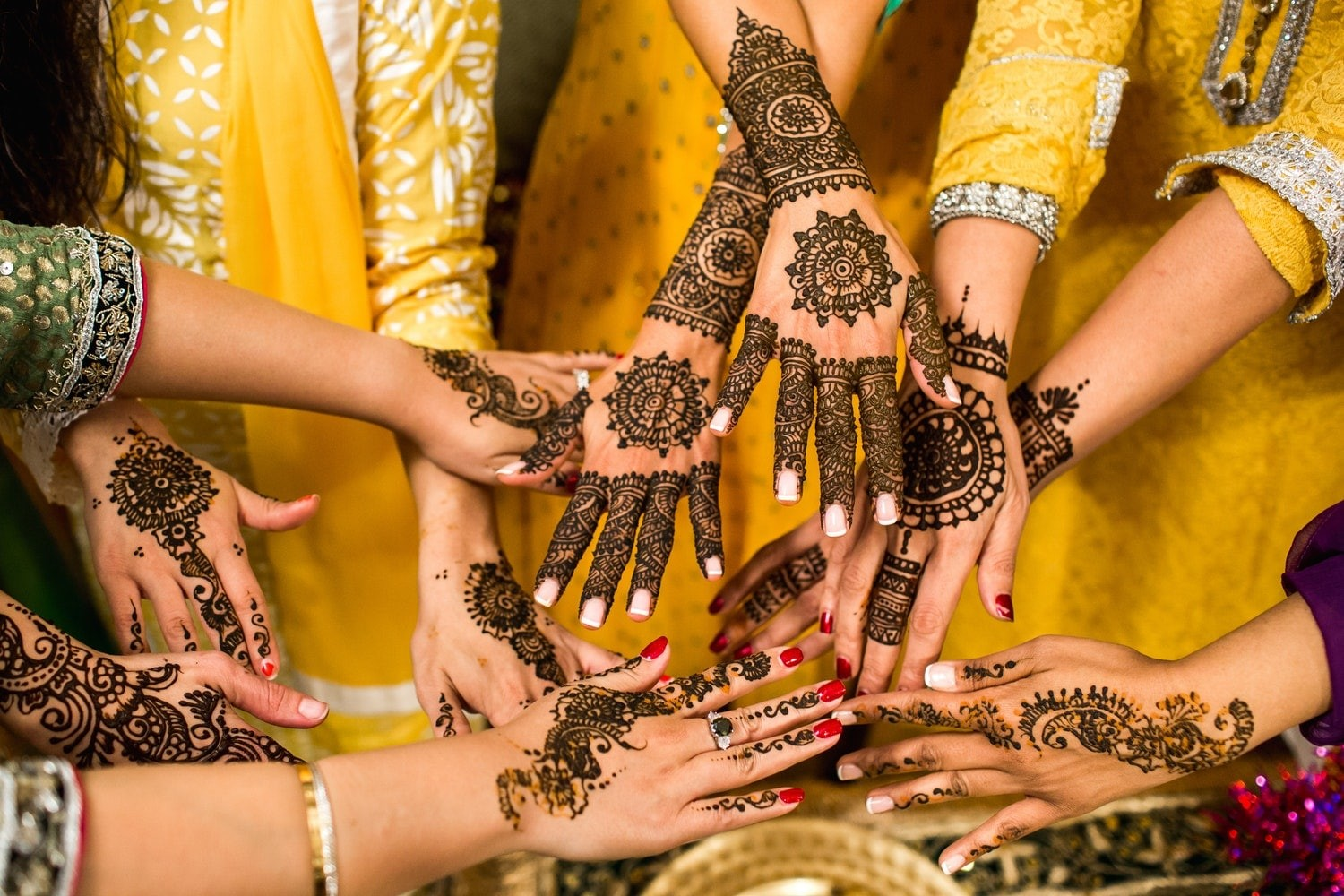 a group of woman's hand, each with henna stain tattoo.
