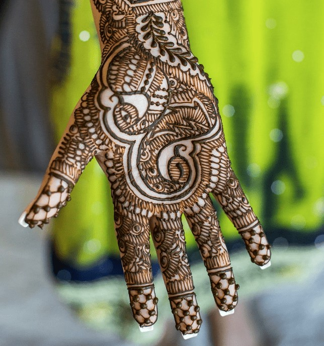 a single hand covered in henna tattoo.