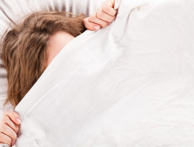 a woman hiding under a white duvet, with her hair, top of her forehead and fingertips exposed.