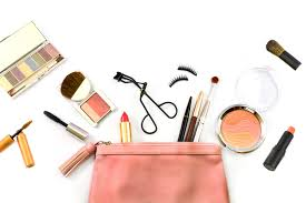 makeup spilled outside of makeup bag with a white background.