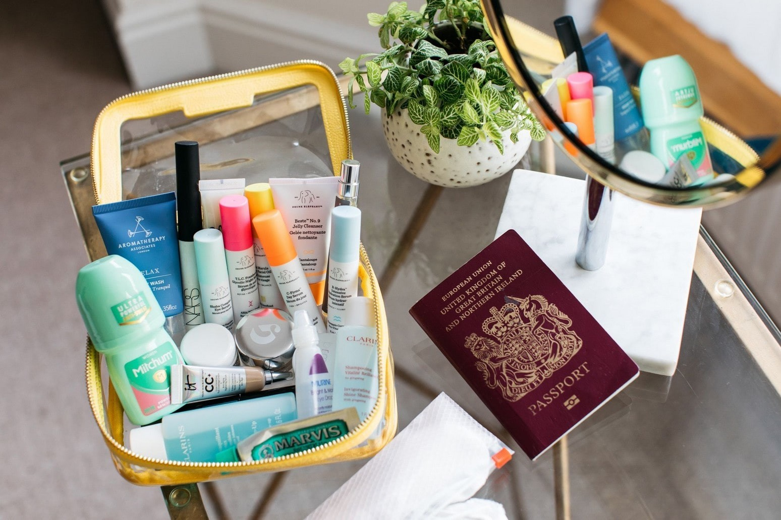 miniatures within a clear plastic makeup bag next to a passport.