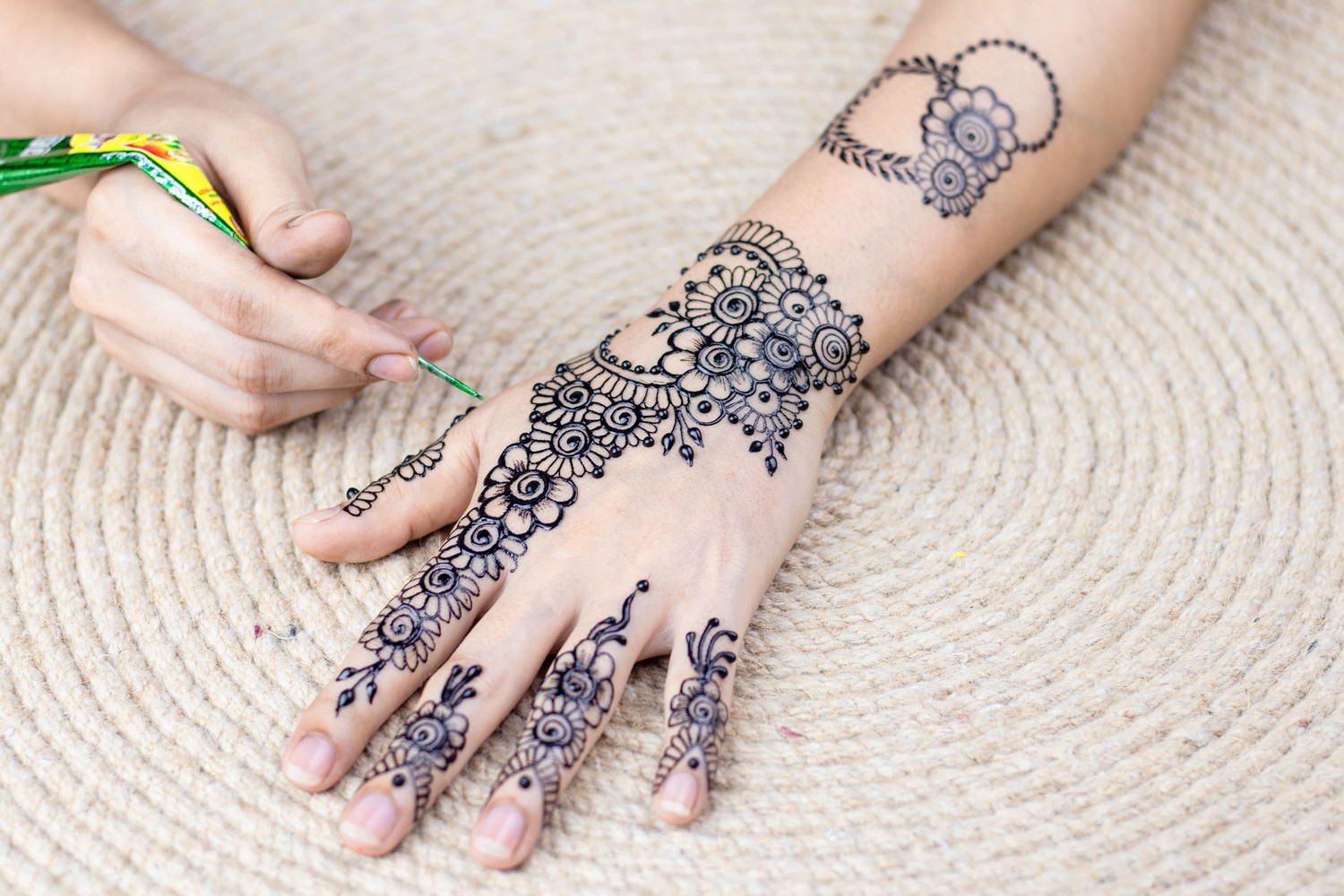 person applying henna stain tattoo to their other hand, with a cream roped rug below.