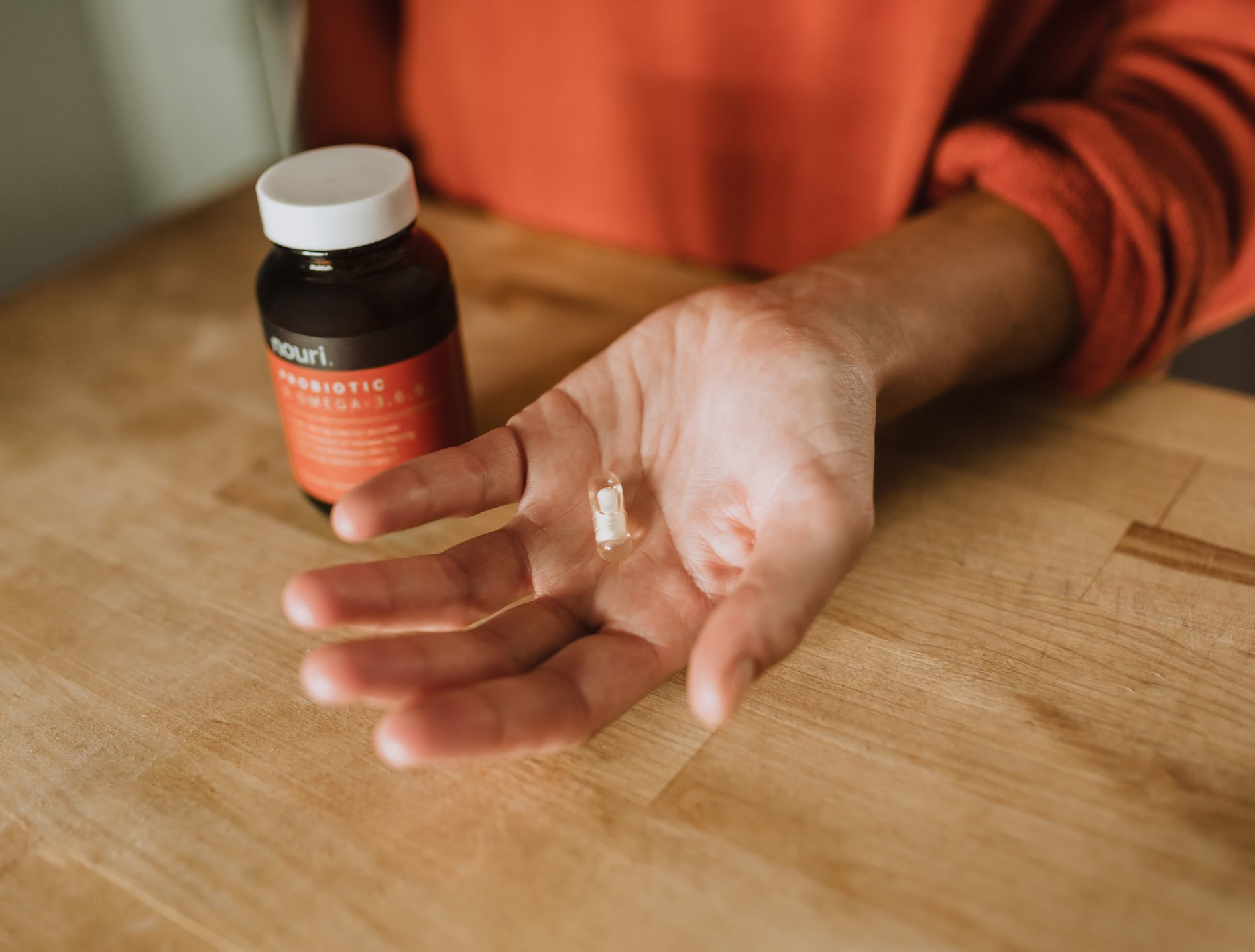 person holding a supplement next to a jar of supplements.