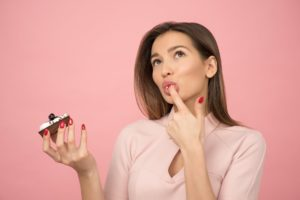 Woman holding a cupcake and licking her finger