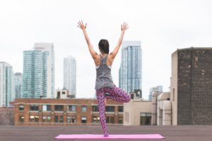 Woman doing a yoga pose on a mat on balcony