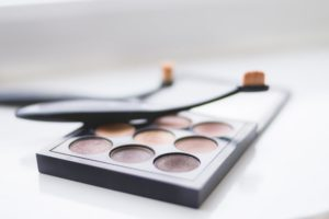 A compact neutral eyeshadow palette with a makeup brush