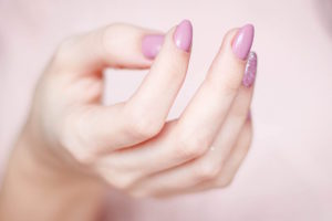 A woman's left hand with pink nail polish