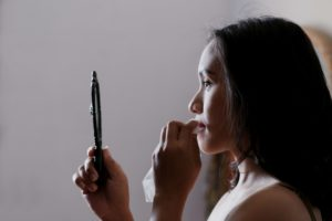 Woman looking in compact mirror and wiping her lips with a face wipe
