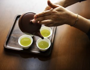 Woman pouring green tea from a pot into cups