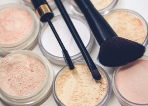 A collection of powders with makeup brushes on top