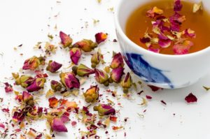 A cup of herbal tea with flower petals nearby and in the tea
