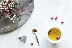 A cup of herbal tea with flowers on the side