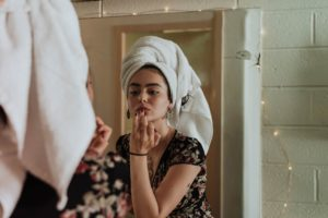 Girl with curly hair wrapped in a white towel as she does her makeup in the mirror