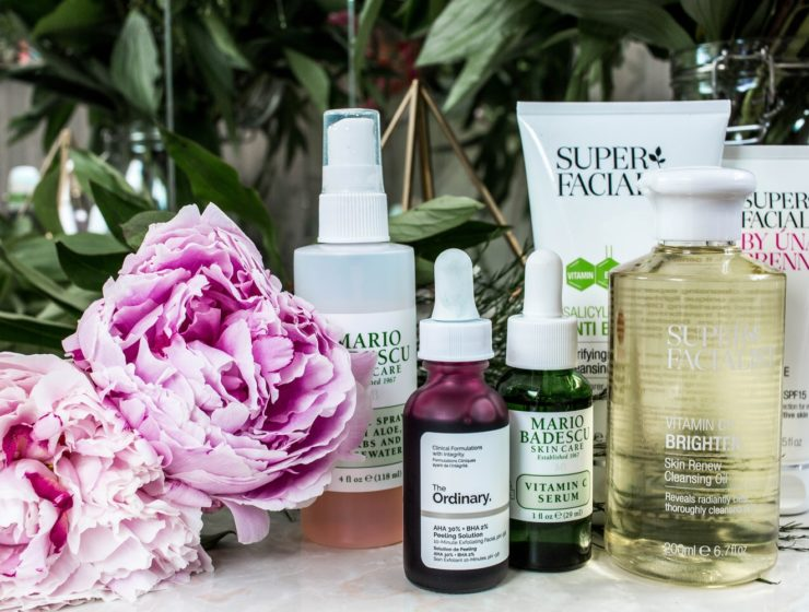 A collection of skincare products with flowers near it