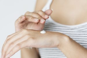 A woman applying cream to her hand