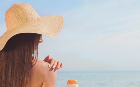Woman wearing a sunhat by the beach and applying sunscreen to her shoulder
