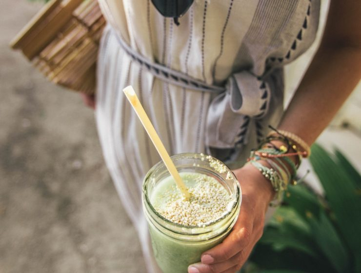 woman holding a green smoothie, with a straw, the surrounding image blurred.