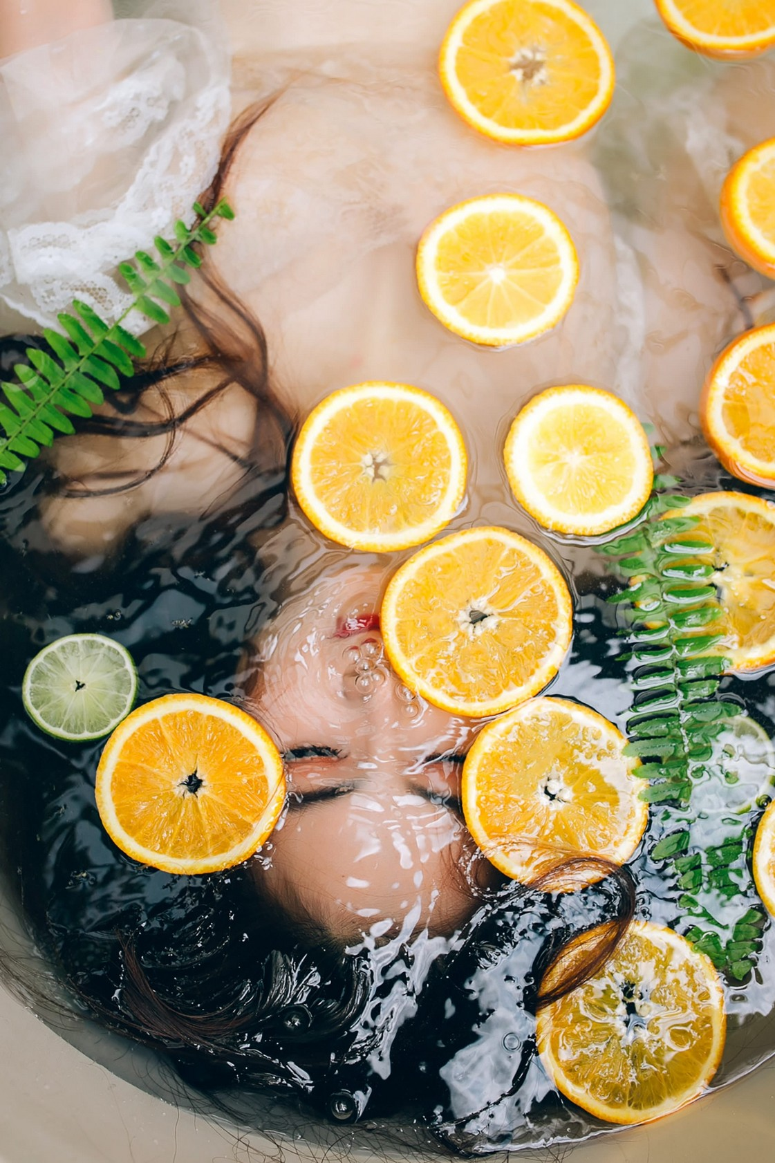 drinks: woman lying in water with lemon slices floating above her face.