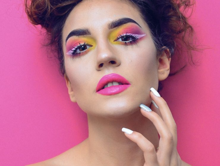 woman wearing vibrant makeup on a pink background,