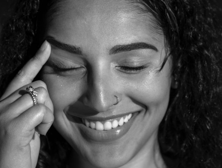 woman smiling whilst pointing to her eyebrow, black and white image.