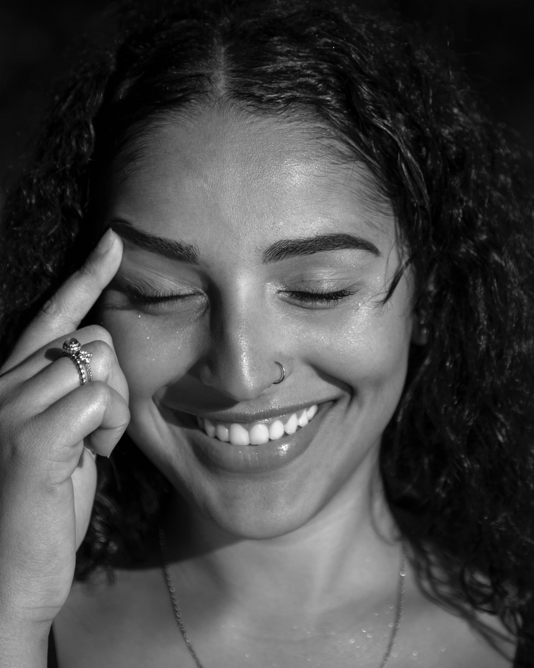woman smiling whilst pointing to her eyebrows, black and white image.