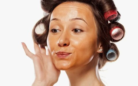 woman wearing makeup too dark for her skin, with rollers in her hair.