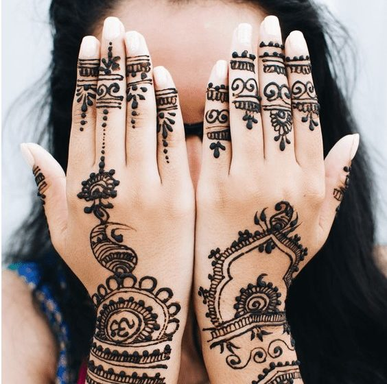 a woman with dark hair and henna over the back of her hands, covering her face with them.