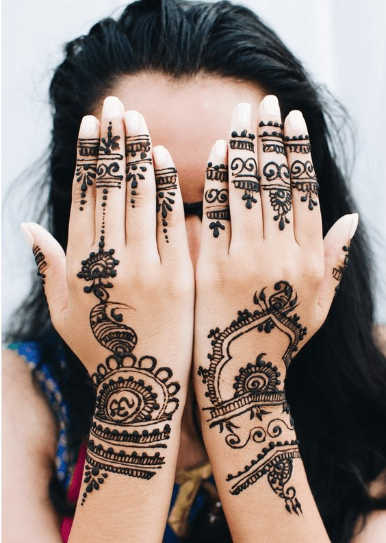 a woman with dark hair and henna stain over the back of her hands, covering her face with them.