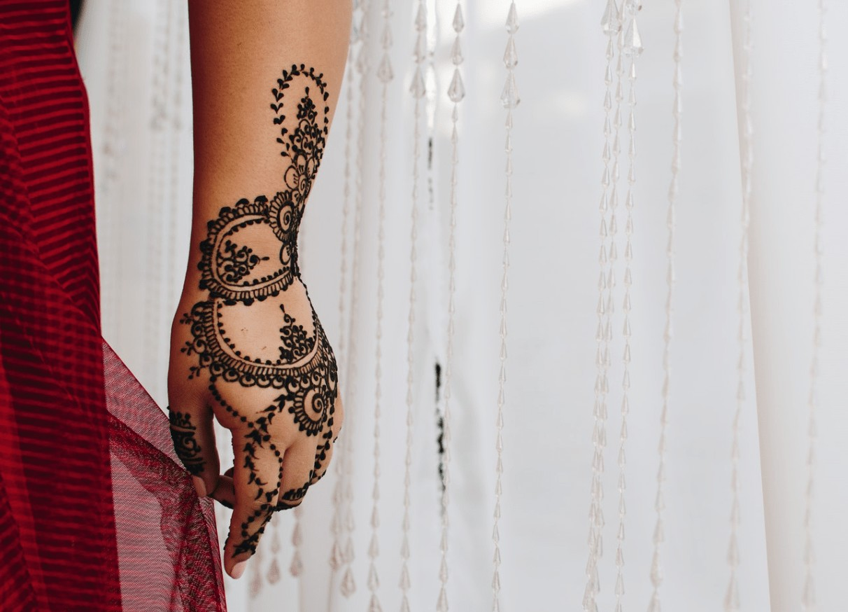 a single hand, in front of a white sheet curtain, whilst covered in henna stain tattoo.