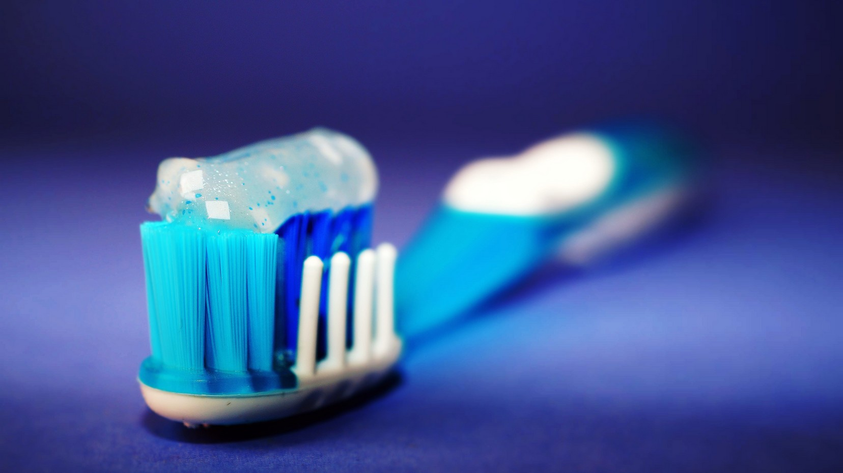 blue toothbrush with clear toothpaste on, with a blue background.