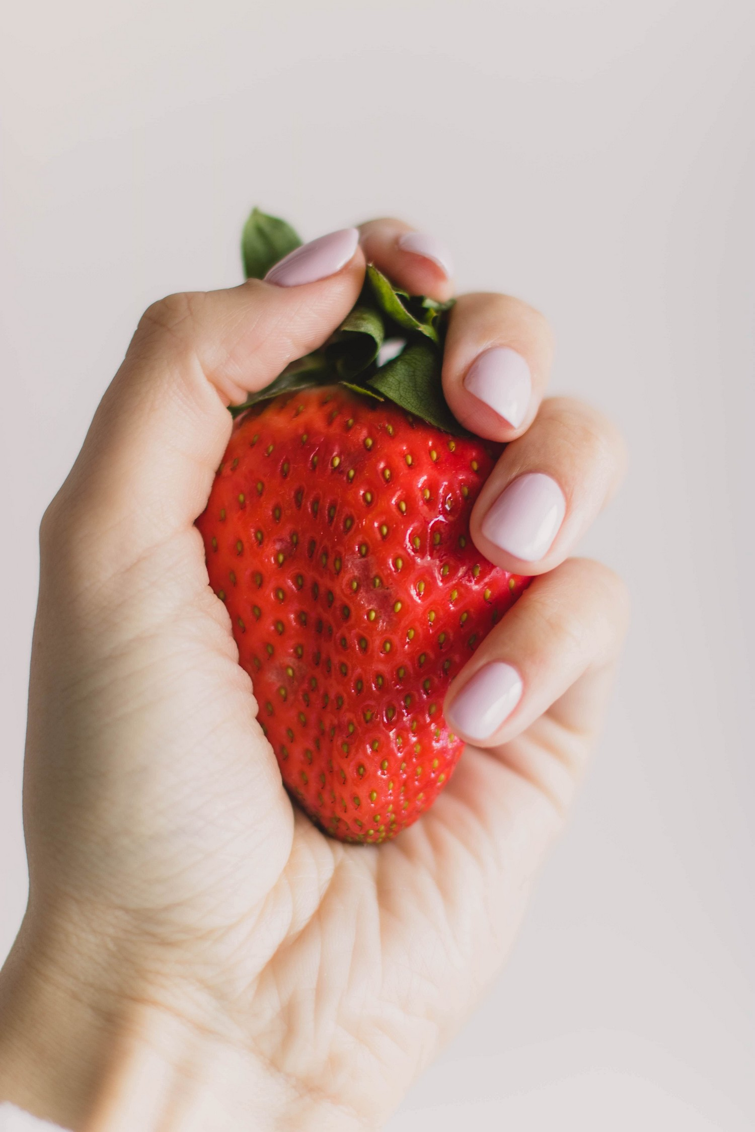 close up of a person holding a strawberry, which is proven to remove coffee stains from teeth.