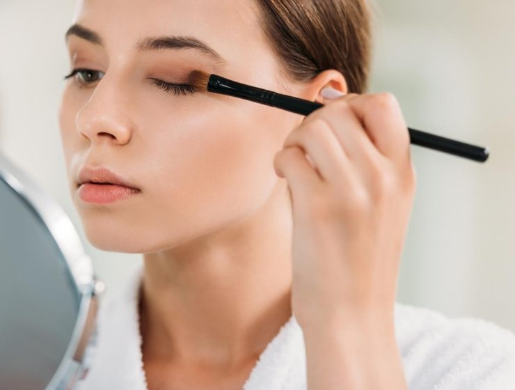 woman applying brown eyeshadow left-handed.