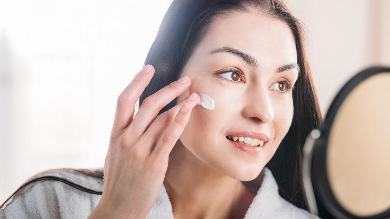 woman applying moisturiser in front of a mirror.