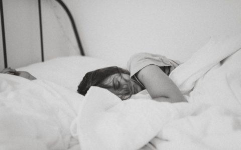 woman lying within white bedding, asleep.