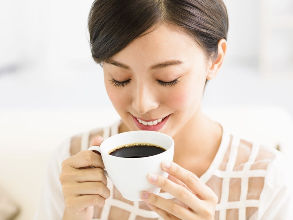 woman with white teeth smiling into her mug of coffee.