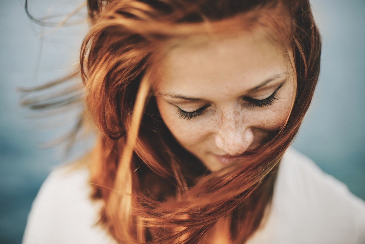 woman with red hair and freckles smiling whilst looking down