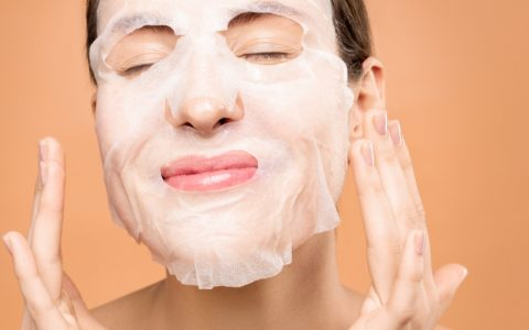 woman wearing a white sheet mask, smiling, prep your skin.