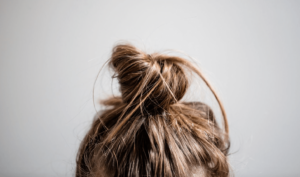 Women with her hair tied in a top bun on top of her head