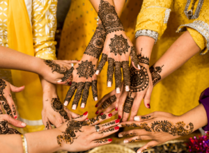Women with henna on their hands and wearing yellow clothes