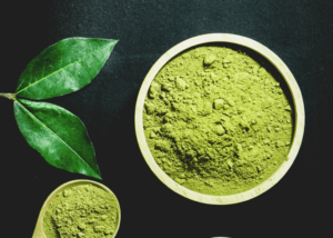 Green henna powder in a bowl with henna leaves near it