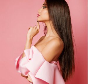 Woman with long brown hair wearing a pink dress