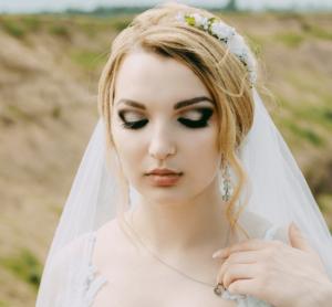 A bride in a wedding dress wearing makeup