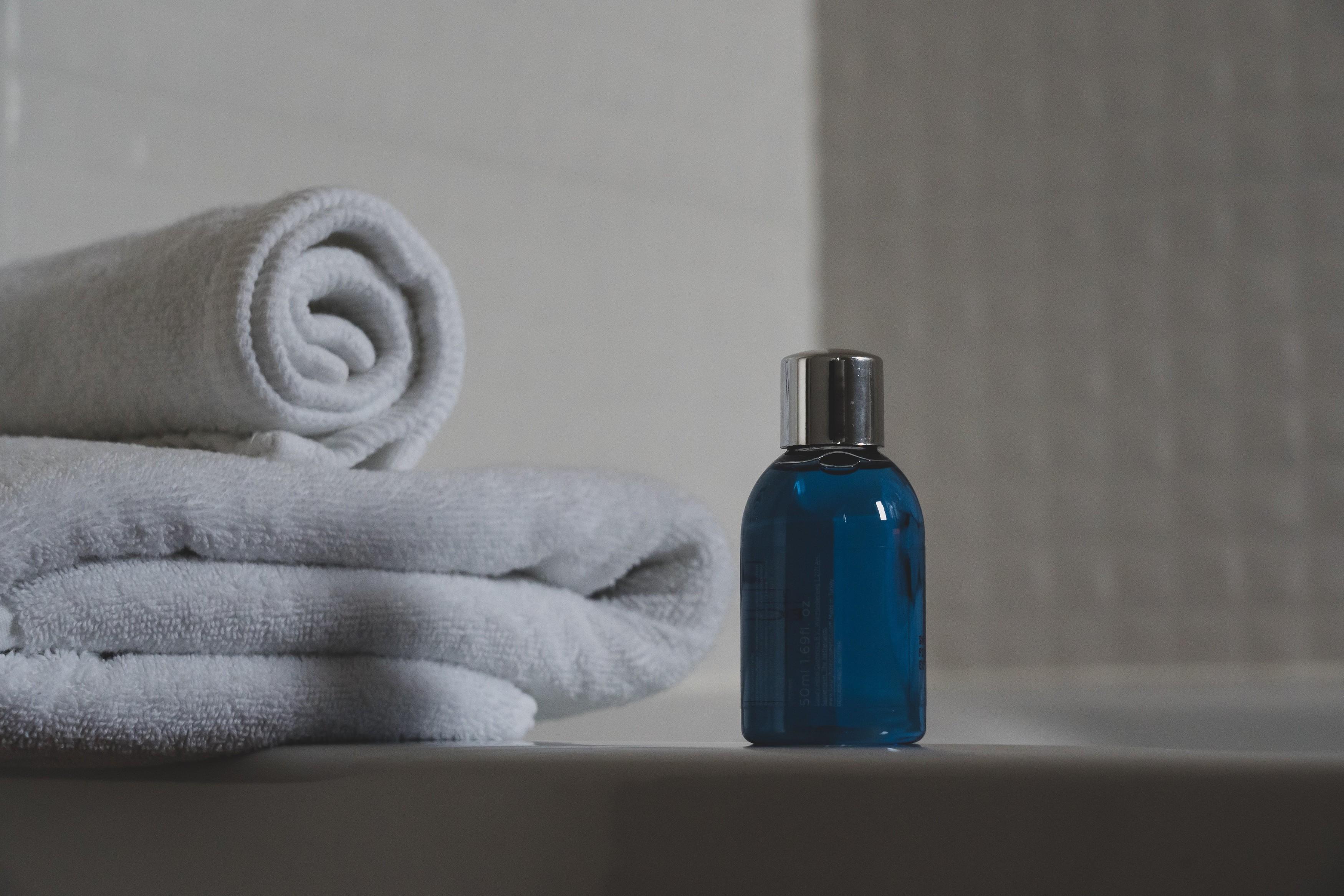 blue glass bottle of body wash beside a white towel.