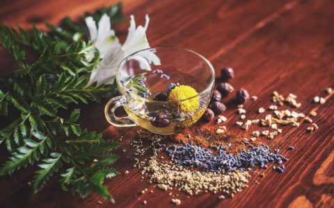 close up of a clear glass on a wooden table with herbal tea, and flowers sprawled around it.