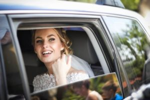 A bride wearing a wedding dress and sitting in a car